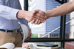 Engineer handshaking for successful deal in construction plan. a. Engineer handshaking for successful deal in construction plan. young architect shake hand for Stock Photos