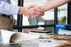 Engineer handshaking for successful deal in construction plan. a. Engineer handshaking for successful deal in construction plan. young architect shake hand for Stock Image