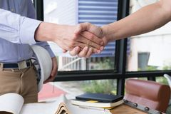 Engineer handshaking for successful deal in construction plan. a. Engineer handshaking for successful deal in construction plan. young architect shake hand for Royalty Free Stock Image