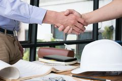 Engineer handshaking for successful deal in construction plan. a. Engineer handshaking for successful deal in construction plan. young architect shake hand for Royalty Free Stock Photography