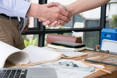 Engineer handshaking for successful deal in construction plan. a. Engineer handshaking for successful deal in construction plan. young architect shake hand for Royalty Free Stock Photos