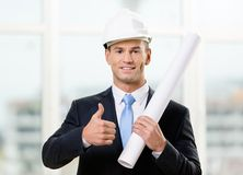 Engineer in hard hat hands layout and thumbs up. Engineer in white hard hat hands layout and thumbs up. Concept of successful construction Royalty Free Stock Photography