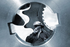 Engineer in hard-hat inside gear axles Royalty Free Stock Images