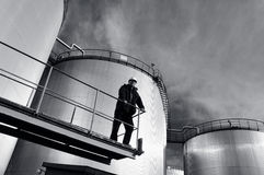 Engineer in hard-hat and oil tanks Royalty Free Stock Images