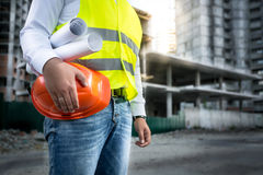 Engineer with hardhat and blueprints posing on building site. Closeup photo of engineer with hardhat and blueprints posing on building site Stock Photography
