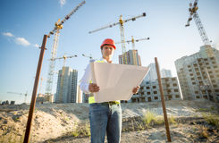 Engineer in hardhat inspecting blueprints on building site Stock Photos