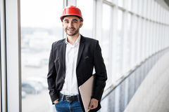 Engineer in hardhat with laptop computer, smiling at camera. Portrait of elegant engineer in hardhat with laptop computer, smiling at camera Stock Image