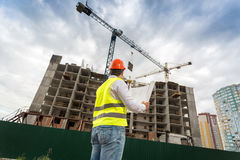 Engineer in hardhat looking at building under construction. Young engineer in hardhat looking at building under construction Royalty Free Stock Image