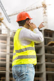 Engineer in hardhat talking by phone and pointing at building si Stock Photography