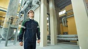 Engineer in hardhat is walking in heavy industry factory.  stock footage