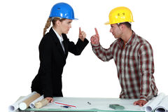 Engineer having an argument. With a tradesman stock images