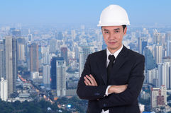 Engineer in helmet with arms crossed, city background Stock Images