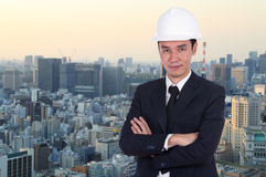 Engineer in helmet with arms crossed, city background Royalty Free Stock Images