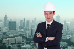 Engineer in helmet with arms crossed, city background Stock Image