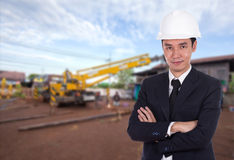 Engineer in helmet with arms crossed, construction site  backgro Royalty Free Stock Images