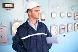 Engineer with helmet and blueprints at control room Royalty Free Stock Photography