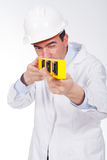 Engineer with a helmet on paying attention and using a lev Stock Photos