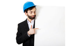 Engineer in helmet pointing on empty banner. Royalty Free Stock Image