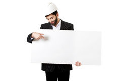 Engineer in helmet pointing on empty banner. Smiling businessman with hard hat pointing on empty banner Royalty Free Stock Photo