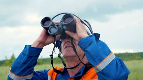 Engineer in helmet watches in binoculars high voltage line in field