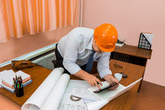 Engineer in helmet working with drawings Stock Photo