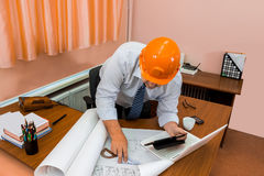 Engineer in helmet working with drawings Royalty Free Stock Photo