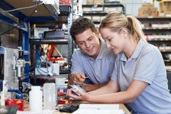 Engineer Helping Female Apprentice In Factory To Measure Component Using Micrometer. Engineer Helps Female Apprentice In Factory To Measure Component Using royalty free stock photography