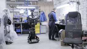 Engineer for his workplace. Creates a modern technical robot. The disassembled case of the robot stands next to the stock video