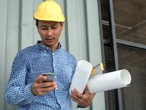 Engineer hold blueprint paper construction drawing plan and holding mobile phone,Architect working in office,Engineering tools on. Desk at site project stock images