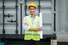 engineer holding blueprint and standing at construction site area. he smile after construction complete. royalty free stock images