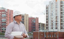 An engineer holding blueprints. On a background with buildings Stock Image
