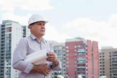 An engineer holding blueprints. On a background with buildings Royalty Free Stock Photo