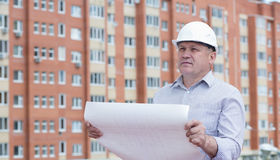 An engineer holding blueprints. On a background with buildings Stock Photo