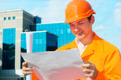 Engineer holding blueprints. With a business center at the background Royalty Free Stock Photography