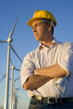 Engineer Holding Blueprints in Front of Modern Wind Turbines Royalty Free Stock Image