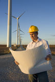 Engineer Holding Blueprints in Front of Modern Wind Turbines Royalty Free Stock Photos