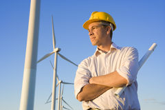 Engineer Holding Blueprints in Front of Modern Wind Turbines Stock Photography