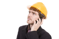 Engineer holding a cellphone with a yellow helmet Stock Images