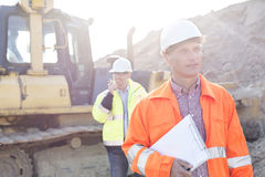Engineer holding clipboard on construction site with colleague in background Royalty Free Stock Images
