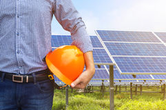 Engineer holding construction helmet front solar photovoltaic power station. Engineer stand holding yellow construction helmet front solar photovoltaic power royalty free stock photo