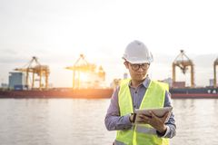 Engineer holding digital tablet control shipping containers cargo, Container freighter docks. Transportation concept royalty free stock photo