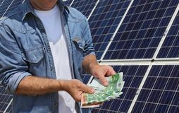 Solar energy panels concept with Euro money. Engineer  holding Euro banknote with photovoltaic solar energy panels in background Stock Photo