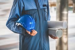 Engineer holding hard hat and blueprint. Engineer on professional wear holding hard hat and blueprint drawing. Engineering people concept Stock Photo