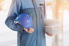 Engineer holding hard hat and blueprint. Engineer on professional wear holding hard hat and blueprint drawing. Engineering people concept Stock Photos