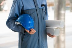 Engineer holding hard hat and blueprint. Engineer on professional wear holding hard hat and blueprint drawing. Engineering people concept Royalty Free Stock Photos