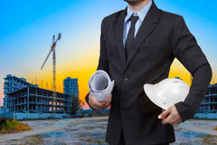 Engineer holding hardhat and blueprint at building construction Stock Images