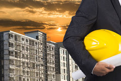 Engineer holding hardhat at building construction Stock Photography