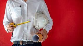 Engineer holding helmet, tape measure and drawing royalty free stock photos