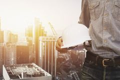 Engineer holding helmet for workers security on background of ne. W buildings and construction cranes on background of evening sunset cloudy sky Silhouette Stock Photos