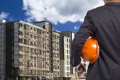 Engineer holding helmet for working at footing of building Royalty Free Stock Photo